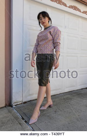 woman in white and purple sweater and black skirt standing near white garage gate during daytime - Stock Photo