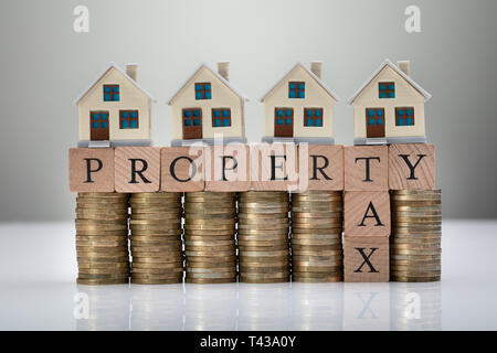 House Models On Stacked Coins Showing Property Tax Concept On White Desk
