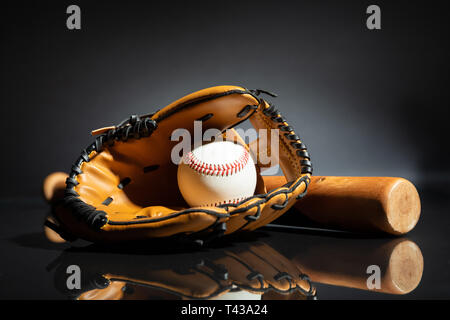 Close-up Of Leather Glove With Baseball And Bat Against Black Background - Stock Photo