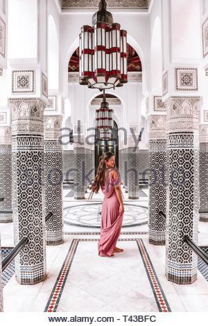 woman standing under chandelier - Stock Photo
