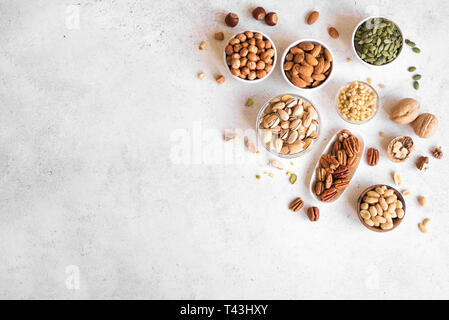 Various Nuts in  bowls on white background, top view, copy space. Pecans, hazelnuts, walnuts, pistachios, almonds, pine nuts, peanuts, pumpkin seeds. - Stock Photo