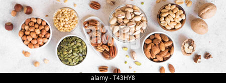 Various Nuts in  bowls on white background, top view, banner. Nuts assortment - pecans, hazelnuts, walnuts, pistachios, almonds, pine nuts, peanuts, p - Stock Photo