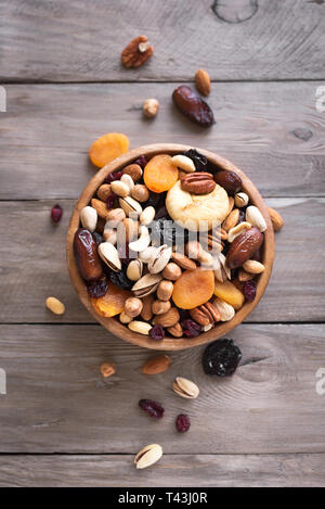 Mixed nuts and dried fruits in wooden bowl on wooden background, top view. Healthy snack - mix of organic nuts and dry fruits. - Stock Photo