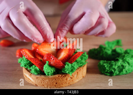 Pastry chef is putting strawberry slices with cream on biscuit making a mini cake. Hands close-up. Baking and industrial food production - Stock Photo