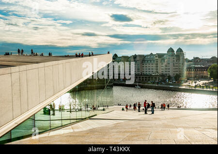 Norway, Oslo August 1, 2013: Tourists take photos and admire the view of the Oslo panorama from the embankment of the Opera house at sunset. Editorial - Stock Photo