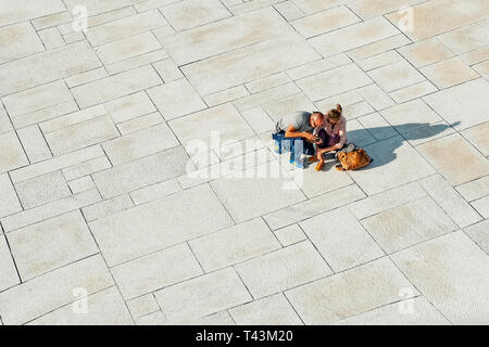 Norway, Oslo August 1, 2013: Two young people tourists relax and view photos on the waterfront of the Opera house in Oslo at sunset. Editorial - Stock Photo