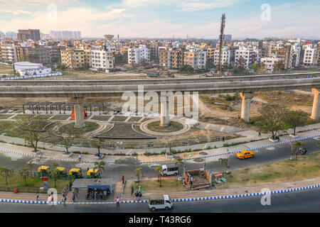 India cityscape aerial view with highway road residential and commercial buildings with view of over bridge and city traffic at sunset - Stock Photo