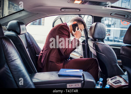 Happy businessman is talking on mobile while driving in his limo car - Stock Photo