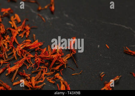 Dried orange red saffron ( Crocus sativus ) flowers on a black board. Space for text in upper right part. - Stock Photo