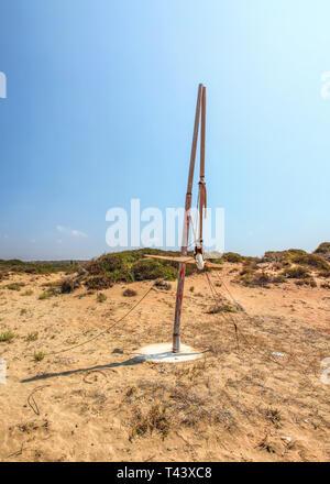 Sun shining to small broken wind power turbine in dry, desert like land. Post apocalyptic wasteland scene. - Stock Photo