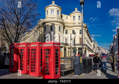 A row of Red public telephone boxes on The Strand at The junction with Duncannon St ,London WC2 - Stock Photo