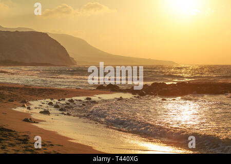 Sunset on empty wild beach. Small waves over rock, hills in hazy background. - Stock Photo