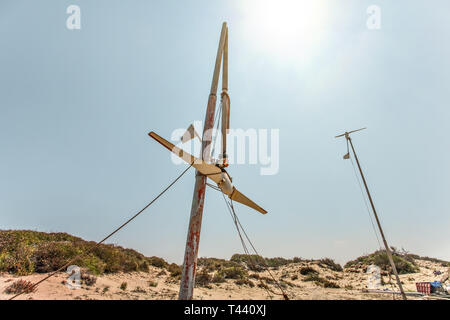 Two small wind turbines, one of them broken, standing on desert, strong back light sun in background. - Stock Photo