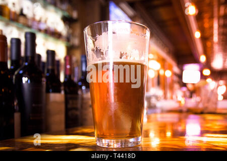 Glass Pint of amber beer with colorful blur of bar in background - Stock Photo