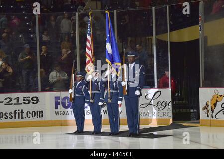 Robins Air Force Base Honor Guard presents the colors at the Macon Mayhem's Military Appreciation ice hockey game, March 16, 2019, in Macon, Georgia. Other base participants included Col. Lyle Drew, Robins Air Force Base Installation Commander, and Chief Master Sgt. Gary Hart, 78th Air Base Wing Command Chief, dropping the puck at the beginning of game, the Robins AFB Honor Guard; MSgt Hollye Williamson, Air Force Life Cycle Management Center, singing the national anthem, and 5th Combat Communications Group doing a military vehicle display. - Stock Photo