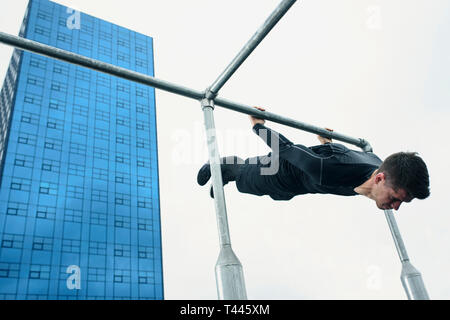Sportsman use street workout zone in  city center for his calisthenic workout. Training on a bar with modern office building in the background. - Stock Photo