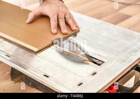 Man cutting laminate floor boards on circular saw, detail on hands holding wooden panel - Stock Photo