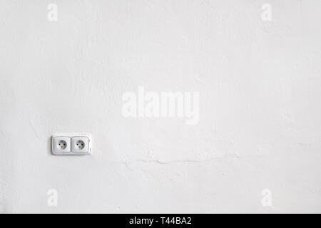 Empty white wall space for text images with two power sockets - Stock Photo