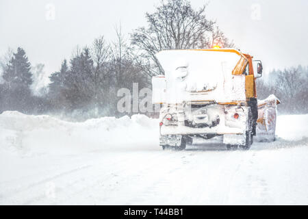 Snow plow gritter cleaning road during heavy winter snow storm - Stock Photo