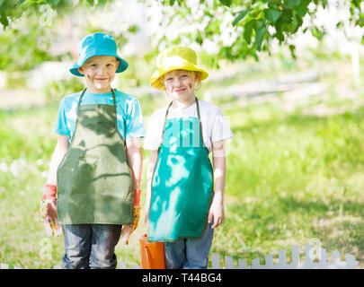 children gardening and watering - Stock Photo