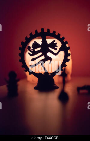 Backlit statuette of the dancing Shiva - Stock Photo