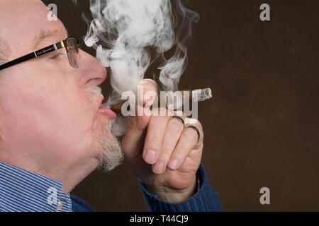 An older man enjoying smoking a good cigar - Stock Photo