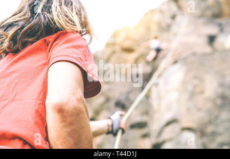 Woman climbing up on mountain cliff while man helping her to climb to the top holding the rope - Climber in action on the rock near the peak - Stock Photo