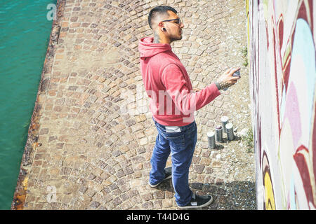 Street graffiti artist painting with a color spray can a graffiti mural on the wall - Urban, lifestyle, street art concept - Stock Photo