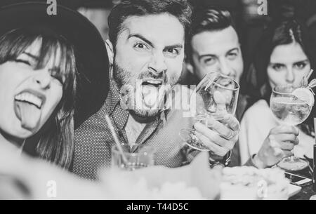 Friends having fun drinking cocktails and taking selfie in the bar - Young people taking photo in the club making silly faces - Stock Photo