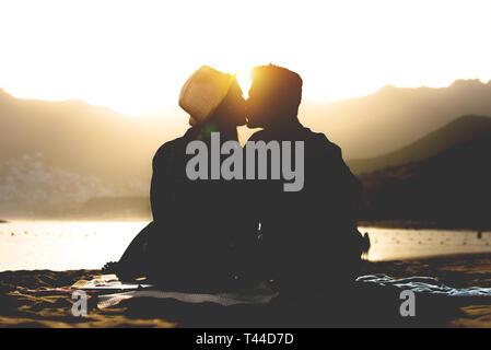 Romantic young couple kissing on the beach on sunset - Silhouette of teens lovers at the beginning of their story sitting on sand - Stock Photo