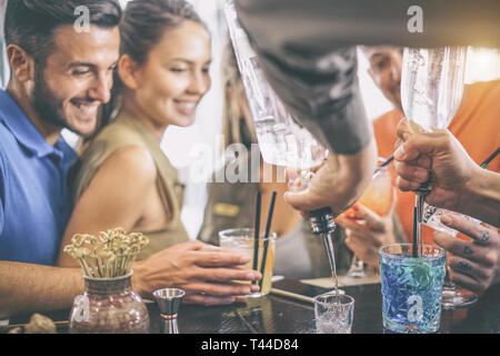 Happy young friends having fun enjoying drinks at bar while barman preparing cocktails and shot - Two couples looking at bartender - Stock Photo
