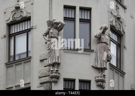 Statues of Two Little Russian (Ukrainian) women depicted on the House at Two Little Russian Women (Dům u dvou Malorusek) in Pařížská Street in Josefov (Jewish Quarter) in Prague, Czech Republic. The dwelling house designed by Czech architect Matěj Blecha was built in 1905-1906. - Stock Photo