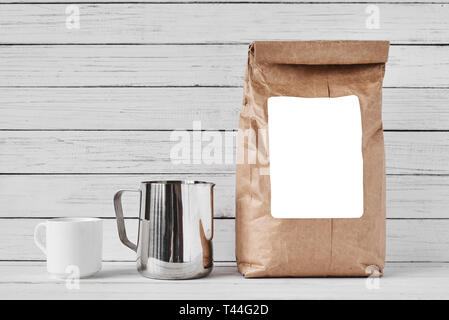 Coffee cup, craft paper bag and stainless pitcher on white background, copy space - Stock Photo
