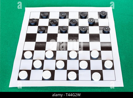 checkers on black and white checkered sheet board on green baize table - Stock Photo