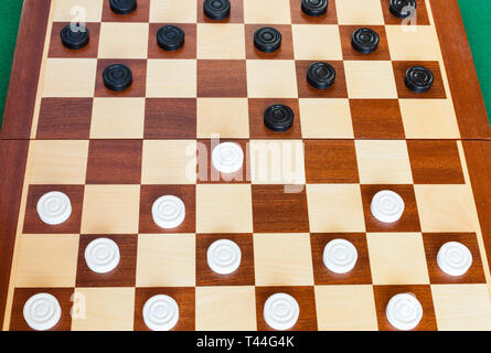 wooden checkered board with draughts on green baize table - Stock Photo