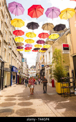 Cherbourg-Octeville, France - August 21, 2018: People walk along the pedestrian shopping street under the Umbrellas of Cherbourg. Normandy France - Stock Photo