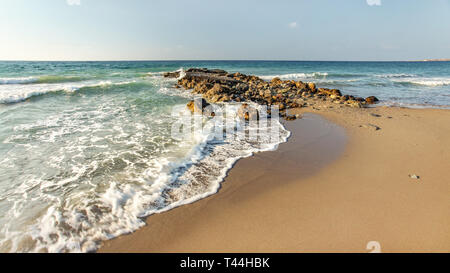 Afternoon sun shines on wild beach, some small waves hitting little rocks in background, empty clean sand spot (space for text) on right side. - Stock Photo