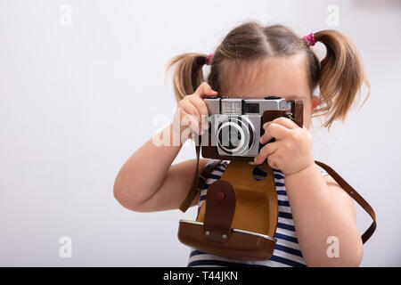 Little Girl Standing Against White Background While Taking Picture Using Photo Camera - Stock Photo