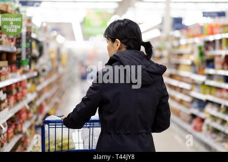 Asian woman doing groceries shopping in supermarket - Stock Photo