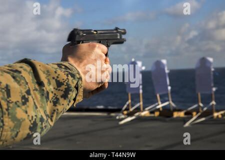 Sgt. Nicholas Nguyen, a rifleman with Alpha Company, Battalion Landing Team, 1st Battalion, 4th Marines, fires during pistol marksmanship qualification aboard the dock landing ship USS Ashland (LSD 48), underway in the South China Sea, Feb. 20, 2019. Nguyen, a native of Oklahoma City, graduated from Putnam City High School in July 2012 before enlisting in July of the same year. Alpha Company Marines are the small boat raid specialists for BLT 1/4, the Ground Combat Element for the 31st Marine Expeditionary Unit. The 31st MEU, the Marine Corps' only continuously forward-deployed MEU partnering  - Stock Photo