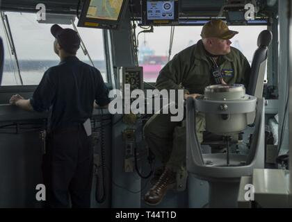 NORFOLK, Va. (Feb. 21, 2019) Capt. Chris Hill, executive officer of the aircraft carrier USS George H.W. Bush (CVN 77), helps navigate from the bridge aboard GHWB as the ship transits the Elizabeth River. GHWB is at Norfolk Naval Shipyard undergoing a docking planned incremental availability (DPIA). - Stock Photo