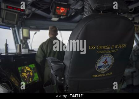 NORFOLK, Va. (Feb. 21, 2019) Capt. Sean Bailey, commanding officer, looks out from the bridge aboard the aircraft carrier USS George H.W. Bush (CVN 77) as the ship transits the Elizabeth River. GHWB is at Norfolk Naval Shipyard undergoing a docking planned incremental availability (DPIA). - Stock Photo