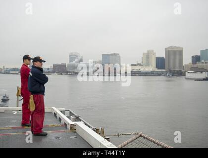 NORFOLK, Va. (Feb. 21, 2019) Electrician's Mate 2nd Class Mason Hill, right, from Wellston, Oklahoma, and Electrician's Mate 3rd Class Ricardo Gutierrez, from Phoenix, Arizona, look out over downtown Norfolk, Virginia aboard the aircraft carrier USS George H.W. Bush (CVN 77) as the ship transits the Elizabeth River. GHWB is at Norfolk Naval Shipyard undergoing a docking planned incremental availability (DPIA). - Stock Photo