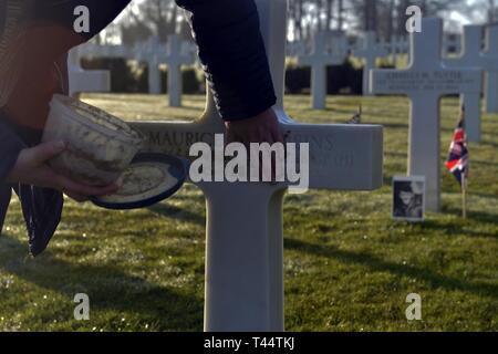 Cambridge American Cemetery associate Tracey Haylock dresses the headstone of Sergeant Maurice Robbins, 'Mi Amigo' B-17 Flying Fortress tail gunner, with sand from Omaha Beach in Normandy, France, during a wreath-laying service at the cemetery, Feb. 22, 2019. Following the ceremony, a four-ship formation of F-15E Strike Eagles from Royal Air Force Lakenheath, England, flew over the cemetery, where more than 3,000 U.S. servicemembers are buried and more than 5,000 are honored on the Wall of the Missing. - Stock Photo