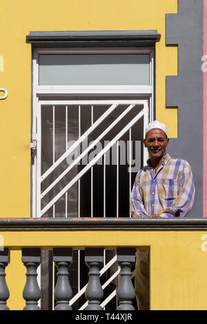 Cape Town, South Africa. March 2019. Man stands on the balcony of his house in the Malay Quarter, Bo-Kaap. Table Mountain can be seen behind. - Stock Photo