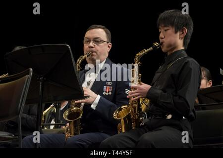 A member of the USAF Band of the Pacific plays alongside a member of the Hamura Daiichi Jr. High School Band during the Japan-U.S. Joint Concert Feb. 24, 2019, at the Hamura Learning Center in Hamura, Tokyo, Japan. Members of the USAF Band of the Pacific and the Hamura Daiichi Jr. High School Band mixed and played as one for the event. - Stock Photo