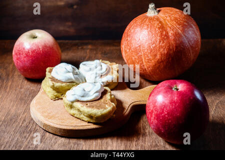 delicious pancakes with sour cream, ripe pumpkin and red apples are on the table. wooden background - Stock Photo