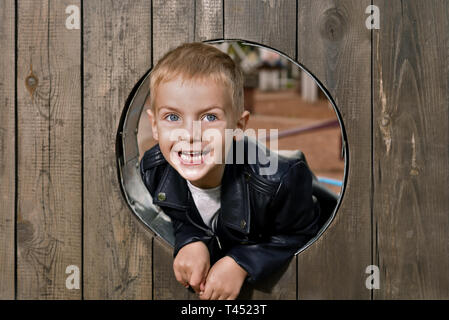 portrait of happy little boy. the kid is looking out of round wooden window and smiling - Stock Photo