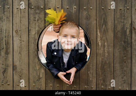 portrait of happy little boy the kid is looking out of round wooden window and smiling - Stock Photo
