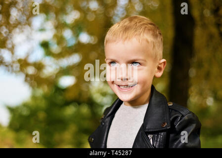 Funny portrait of little sly boy in black leather jacket. autumn season - Stock Photo